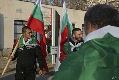 Local citizens draped in Bulgarian national flags gather in sign of protest at the fence of the Harmanli registration center as Bulgarian army soldiers are deployed in Harmanli, Bulgaria, Nov. 25, 2016. Hundreds of migrants have been detained after c...