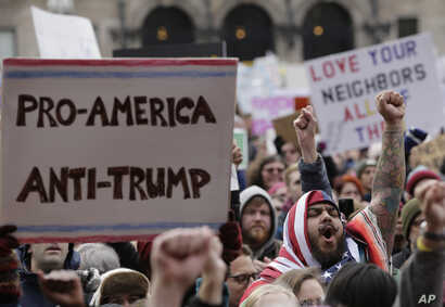 FILE - Izzy Berdan, of Boston, center right, wears an American flags as he raises his arm and chants slogans with other demonstrators during a rally against President Donald Trump's order that restricts travel to the US, Jan. 29, 2017, in Boston.