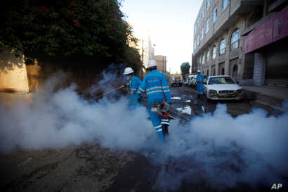 FILE - Public health workers spray insecticide amid fears of a new cholera outbreak in Sanaa, Yemen, June 7, 2018.