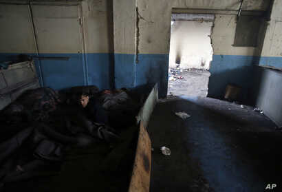 A migrant wakes up after spending the night inside a crumbling warehouse that has served as a makeshift shelter for hundreds of men trying to reach Western Europe in Belgrade, Serbia, Jan. 12, 2017. Migrants have been exposed to freezing temperatures...