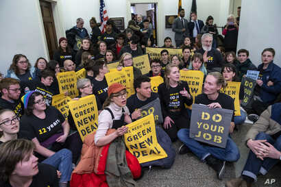 Environmental activists occupy the office of Rep. Steny Hoyer, D-Md., the incoming majority leader, as they try to pressure Democratic support for a sweeping agenda to fight climate change, on Capitol Hill in Washington, Dec. 10, 2018.