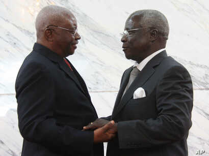 Mozambique President Arnando Guebuza, left, and former Renamo rebel leader Afonso Dhlakama, right, shake hands after signing a peace accord, Sept. 5, 2014.