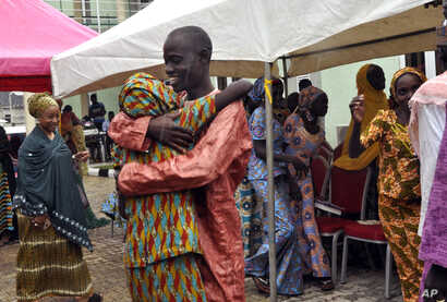 One of freed Chibok girls is embraced by a family member during their reunion in Abuja, Nigeria, Oct. 16, 2016.