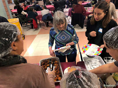 Furloughed government workers, contractors and their families attended a free community dinner donated from families and community organizations during the partial U.S. government shutdown at Montgomery Blair High School in Silver Spring, Maryland, J...