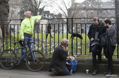 People listen and watch on their mobile devices as Scotland's First Minister Nicola Sturgeon demands a new independence referendum, outside Bute House, in Edinburgh, March 13, 2017.