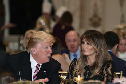 President Donald Trump and first lady Melania Trump talk while having Thanksgiving Day dinner at their Mar-a-Lago estate in Palm Beach, Fla., Nov. 22, 2018.
