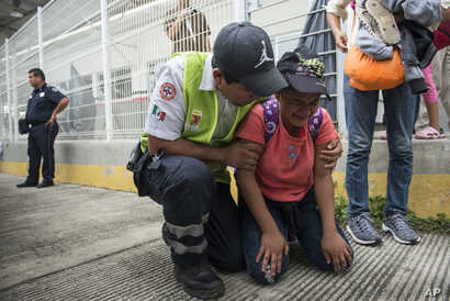A Honduras migrant is comforted by a Mexican paramedic after her mother fainted while crossing the border between Guatemala and Mexico, in Ciudad Hidalgo, Mexico, Oct. 20, 2018.