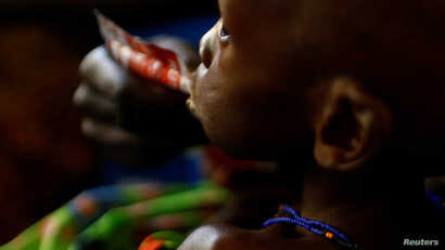 A mother feeds her child with a peanut-based paste for treatment of severe acute malnutrition in a UNICEF supported hospital in the capital Juba, South Sudan, January 25, 2017.