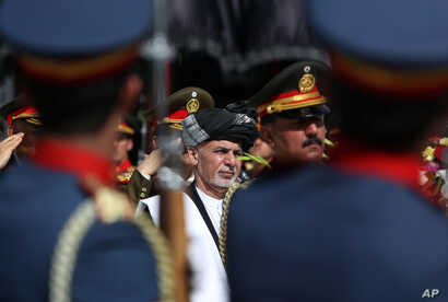 Afghanistan's President Ashraf Ghani, center, inspects the honor guard during the Independence Day celebrations at the Defense Ministry in Kabul, Afghanistan, Thursday, Aug 18, 2016.