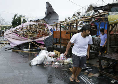A resident walks past damaged stalls at a public market as Typhoon Mangkhut barreled across Tuguegarao city in Cagayan province, northeastern Philippines, Sept. 15, 2018.