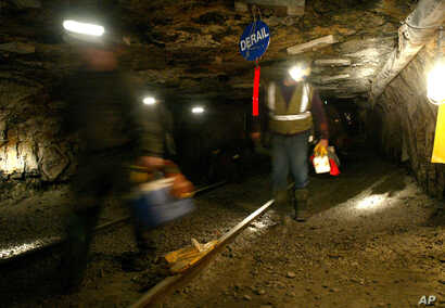 FILE - Ohio coal miners head into the mine for a shift inside the Hopedale Mine near Cadiz, Ohio, March 10, 2006. An election-year bill that would protect health-care and pension benefits for more than 100,000 retired coal miners is dividing coal-sta...