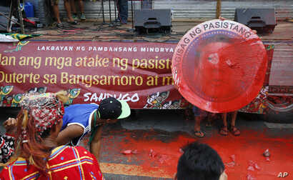 Indigenous people, including Muslims from the besiege city of Marawi, throw red paint at the mock seal of President Rodrigo Duterte to protest the continued siege and the martial law imposed by Duterte on the Mindanao region, Aug. 31, 2017, in Manila...