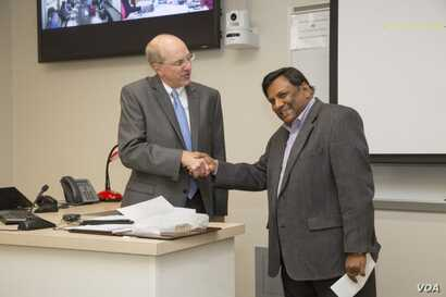 Ashim Mitra, right, discovers he was selected for a President's Award. (Photo by Janet Rogers / Strategic Marketing and Communications)