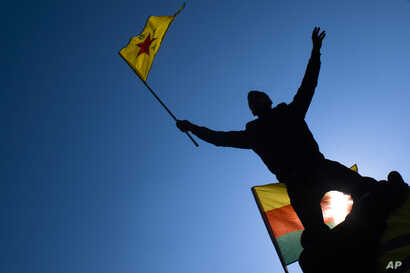 FILE - A man waves a flag with Kurdish symbols as he attends a demonstration of about 1,000  protesters against the Turkish offensive targeting Kurds in Afrin, northern Syria, in Berlin, March 3, 2018.