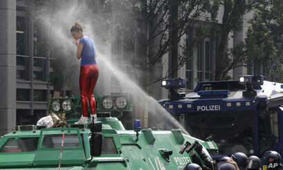 A woman is pepper-sprayed by police after she climbed an armored police vehicle on the first day of the G-20 summit in Hamburg, northern Germany, July 7, 2017.