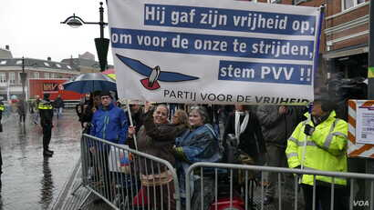 """Rally participant Susan Pfaff-Bons created a banner reading """"He gave up his freedom to fight for ours. Vote Freedom Party,"""" in Breda, Netherlands, March 2017. (M. van der Wolf/VOA)"""