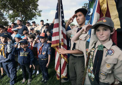 FILE - Boy Scouts and Cub Scouts salute the flag during ceremonies at the Los Angeles National Cemetery in Los Angeles on May 26, 2018.