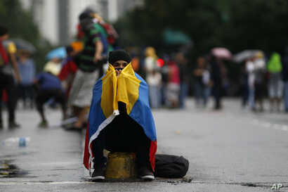 A masked anti-government protester, with a Venezuelan national flag wrapped around him, sits on the edge of a median strip in Caracas, Venezuela, June 28, 2017.