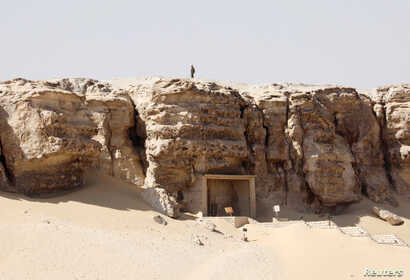 A member of security personnel stands atop a cliff as he guards the area during the presentation of a new discovery at Tuna el-Gebel archaeological site in Minya Governorate, Egypt, Feb. 2, 2019.