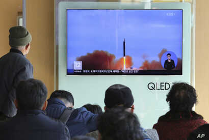 People watch a TV screen showing file footage of North Korea's missile launch at Seoul Railway Station in Seoul, South Korea, Nov. 21, 2017.