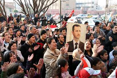 Pro-Syrian regime protesters in the flashpoint city of Homs in central Syria, Thursday, Dec. 29, 2011
