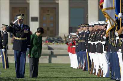 South Korean President Park Geun-hye bows to the colors as she reviews the troops during a full military honors parade to welcome her at the Pentagon in Washington, Oct. 15, 2015.