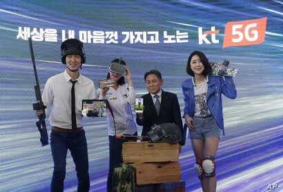 Lee Pil-jae, second from right, vice president at KT Corp., and models introduce various 5G services available on smarpthones during a press conference on 5G service at KT Corp.'s headquarters in Seoul, South Korea, April 2, 2019.