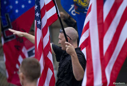FILE - A member of a white supremacy group gives a fascist salute during a gathering in West Allis, Wisconsin, Sept. 3, 2011.