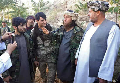 A foreign Islamic State group fighter (2nd-R) speaks to a journalist after he surrendered to government security forces in the Darzab district of Jawzjan province, north of Kabul, Afghanistan, Aug. 1, 2018.