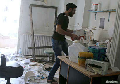 A man removes medicine inside al-Quds hospital after it was hit by airstrikes, in a rebel-held area of Syria's Aleppo, April 28, 2016.