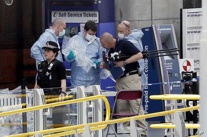 Forensic officers investigate the scene near the Manchester Arena, Manchester, England, May 23, 2017, the day after the suicide attack at an Ariana Grande concert that left 22 people dead as it ended on Monday night.