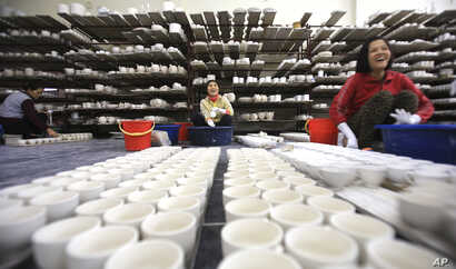 FILE - Workers coat potteries with enamel in a factory in Bat Trang village, Hanoi, Vietnam. Foreign and local businesses hope Vietnam's ruling Communist Party will modernize an economy dominated by state companies.