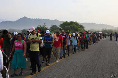Migrants walk along the road after Mexico's federal police briefly blocked the highway in an attempt to stop a thousands-strong caravan of Central American migrants from advancing, outside the town of Arriaga, Mexico, Oct. 27, 2018.