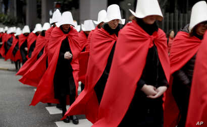 """FILE - Women in favor of a measure to expand legal abortions, wearing red cloaks and white bonnets like the characters from the novel-turned-TV series """"The Handmaid's Tale"""", march in silence to Congress, in Buenos Aires, Argentina, July 25, 2018."""