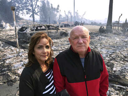 Linda and John Keasler pose for a photo in front of the ruins of their home at the Hawaiian Village Apartments, destroyed when the Thomas fire swept through Ventura, California, Dec. 5, 2017.