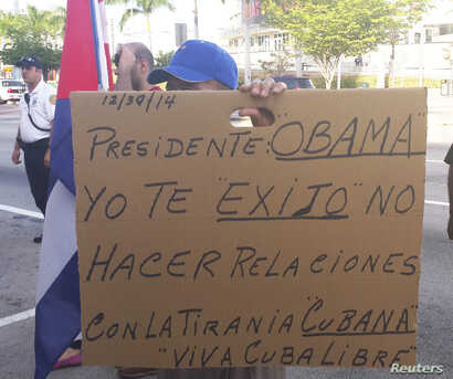 FILE - A protester holds up a sign asking President Obama not to renew relations with Cuba during a rally in solidarity with Cuban dissidents in downtown Miami, Florida.