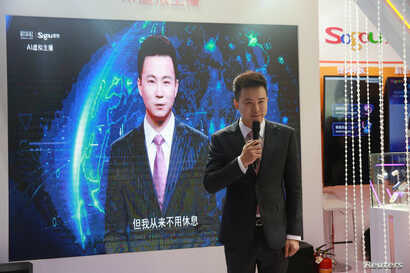 Xinhua news anchor Qiu Hao stands next to an AI virtual news anchor based on him, at a Sogou booth during an expo at the fifth World Internet Conference in Wuzhen town of Jiaxing, Zhejiang province, China, Nov. 7, 2018.