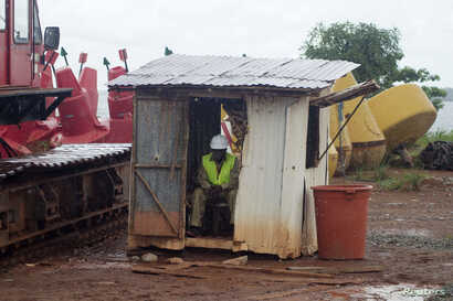 FILE - A worker sits in a hut as it rains at the African Minerals Limited port in Pepel, Sierra Leone.