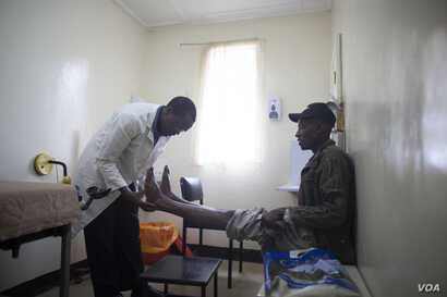 An occupational therapist at The Plaster House examines a patient in Tanzania.