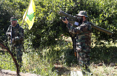 A Hezbollah fighter holds an Iranian-made anti-aircraft missile, right, as he takes his position with his comrade  between orange trees, at the coastal border town of Naqoura, south Lebanon, April 20, 2017.