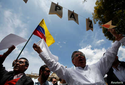 """Supporters of the peace deal signed between the government and Revolutionary Armed Forces of Colombia rebels display a Colombian flag during a rally in front the Narino Palace, in Bogota, Colombia, Oct. 5, 2016. The placards read """"Peace."""""""