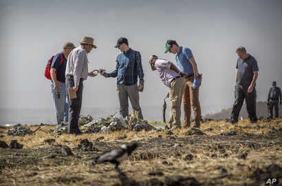 Foreign investigators examine wreckage at the scene where the Ethiopian Airlines Boeing 737 Max 8 crashed shortly after takeoff on Sunday killing all 157 on board, near Bishoftu, or Debre Zeit, south of Addis Ababa, in Ethiopia, March 12, 2019.
