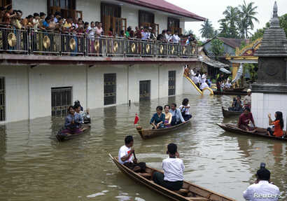 Myanmar opposition leader Aung San Suu Kyi, center, rides a boat as she leaves after visiting a monastery where flood victims are sheltered in Bago, 80 kilometers (50 miles) northeast of Yangon, Myanmar, Monday, Aug. 3, 2015. A report issued Saturday...