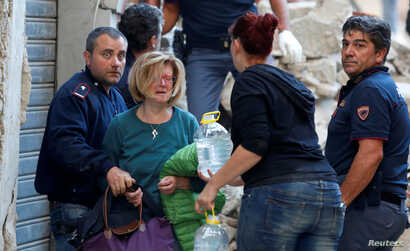 A woman (2nd L) cries after she was rescued from her home following a quake in Amatrice, central Italy, Aug.24, 2016.