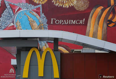 """The logo of McDonald's is seen in front of a house decorated with graffiti reading """"We are proud!"""" and depicting the Order of Victory and a St. George's Ribbon, a symbol widely associated in Russia with the commemoration of victory in World War II, i..."""