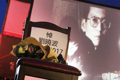 A bouquet of flowers is placed on a chair that reads ''Mourning Liu Xiaobo'' in front of his image during a ceremony to mourn late Nobel Peace Prize laureate Liu, China's most famous political prisoner, at Democracy Square in Taipei, Taiwan, July 14,...