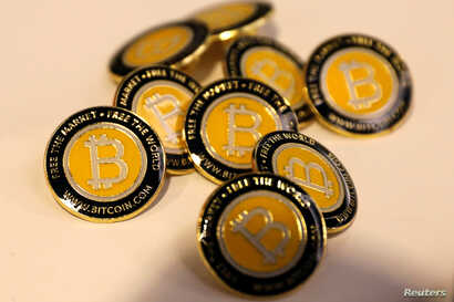 FILE - Bitcoin.com buttons are seen displayed on the floor of the Consensus 2018 blockchain technology conference in New York City, New York, May 16, 2018.