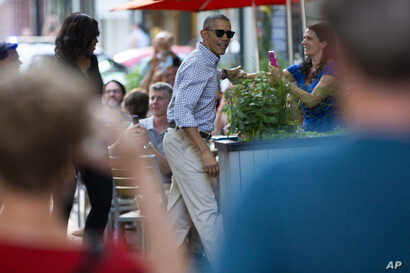 FILE - People take photographs as President Barack Obama, center, and first lady Michelle Obama walk into the Oyamel Cocina Mexicana restaurant in Washington for dinner, May 28, 2016.