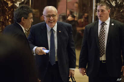 Former New York Mayor Rudy Giuliani, center, smiles as he leaves Trump Tower, Nov. 11, 2016, in New York.