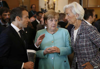 French President Emmanuel Macron, left, speaks with German Chancellor Angela Merkel, center, and Managing Director of the International Monetary Fund Christine Lagarde, right, as they attend a round table meeting of G7 leaders in Taormina, Italy, May...